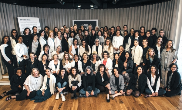 100 women wearing black and white EILEEN FISHER tops gathered together on a stage smiling at the camera