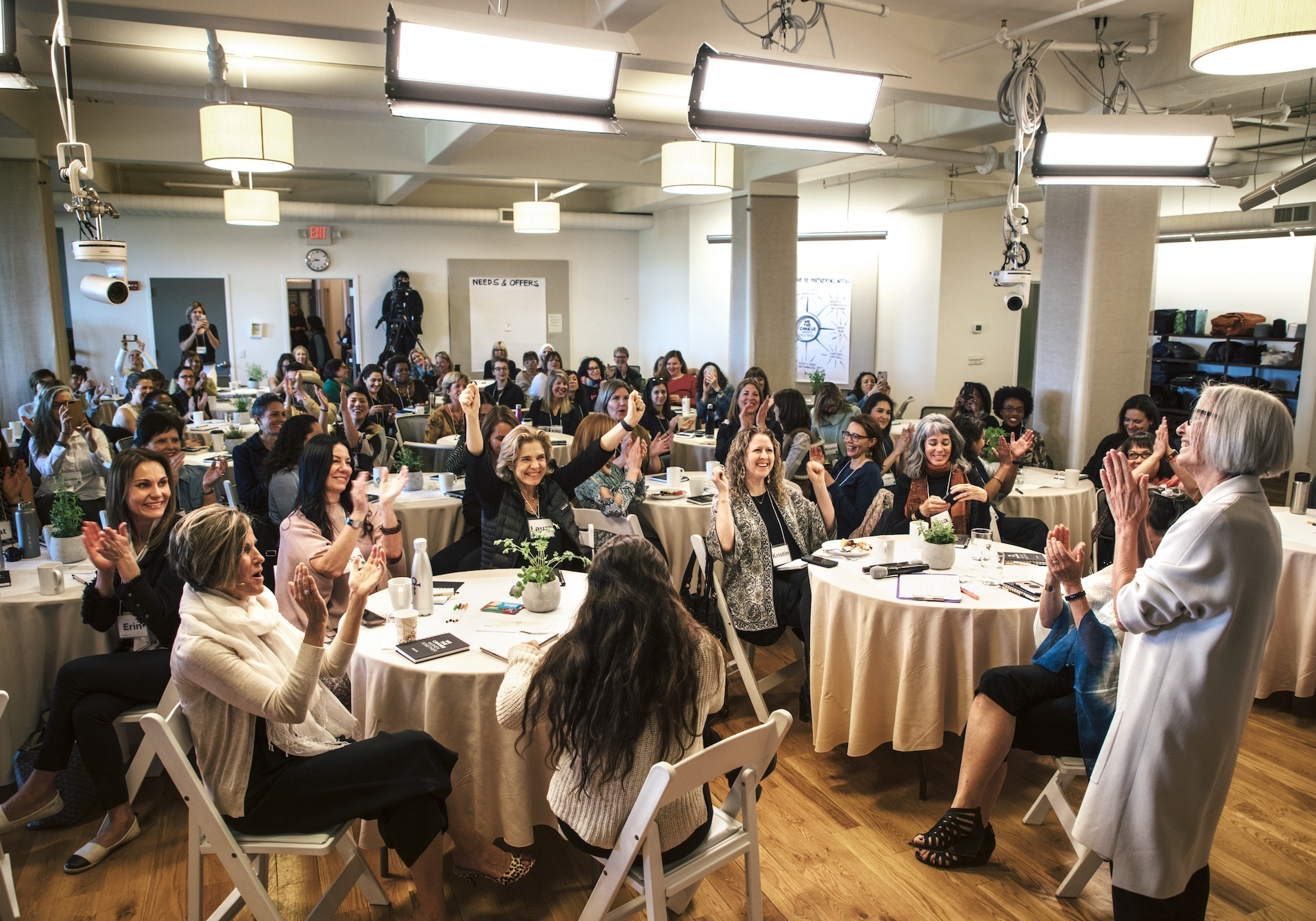 A room full of clapping and cheering women sitting at round tables